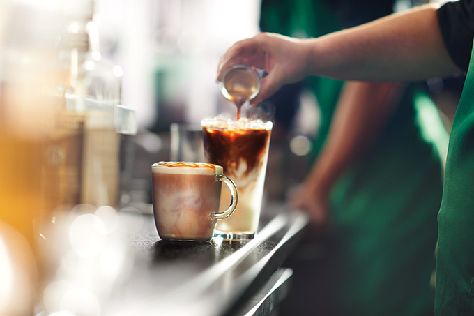 Starbucks employee preparing a Caramel Macchiato